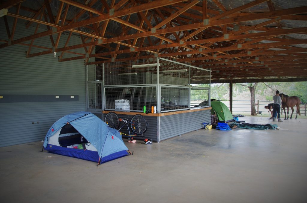 In an open-sided large modern shed, two tents are pitched. Two people with a horse in the background.