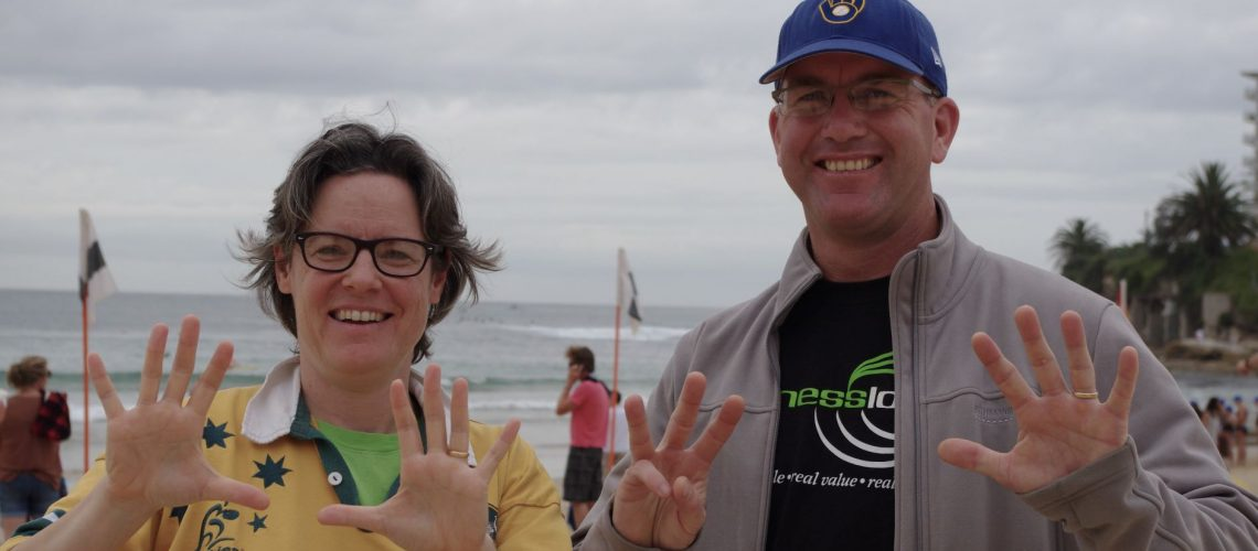 A woman holds up 10 fingers, a man holds up 8 they are standing on a beach, you can see the ocean behind them.