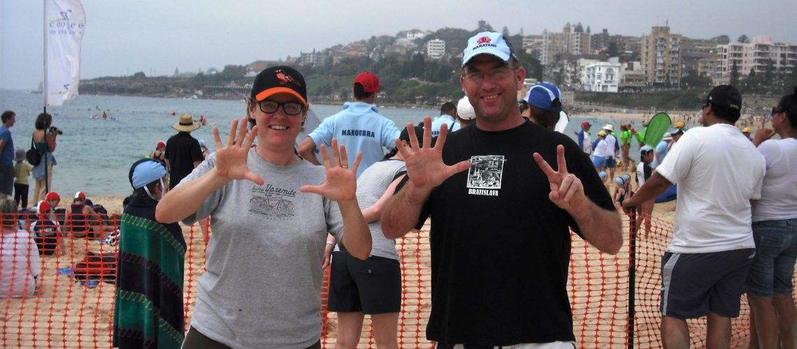 A woman holds up 10 fingers, a man holds up 7 - they are on a crowded beach