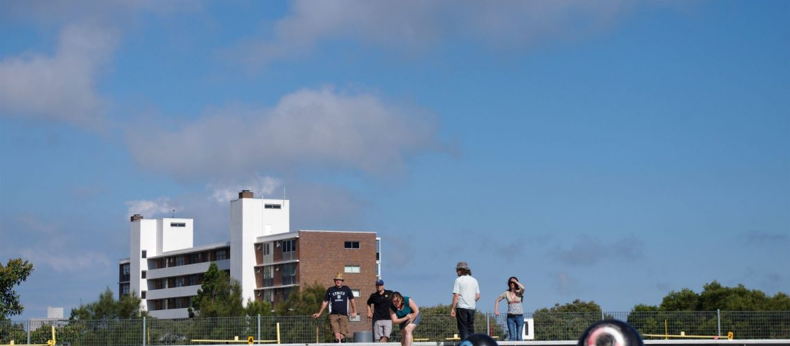 Looking up a lawn bowls rink from ground level as woman in distance bowls ball and others look on