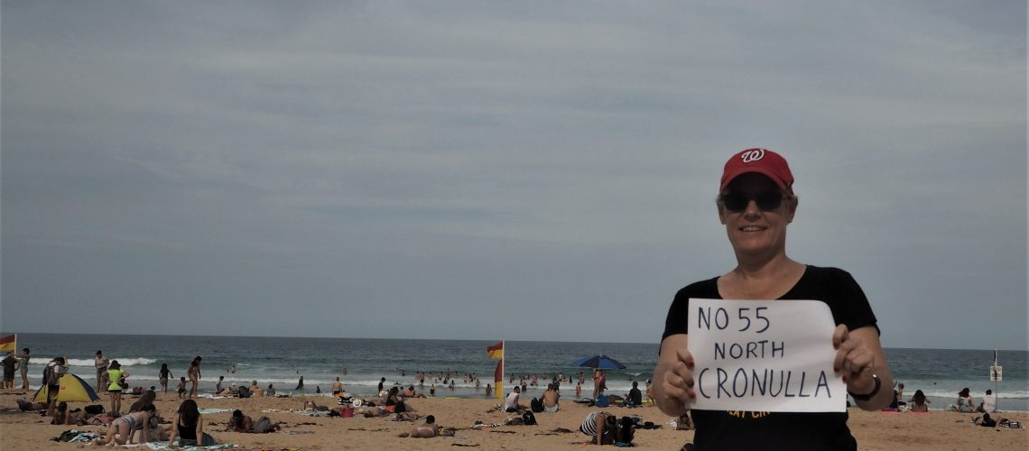 Me holding North Cronulla No 55 sign on beach