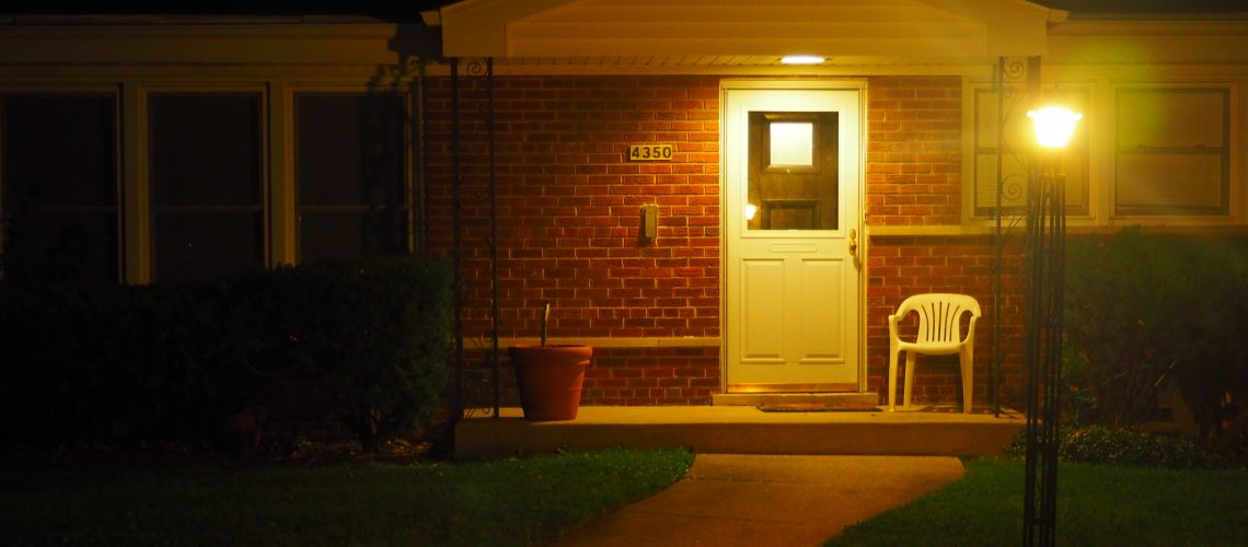 American suburban home at night, lit by porch light